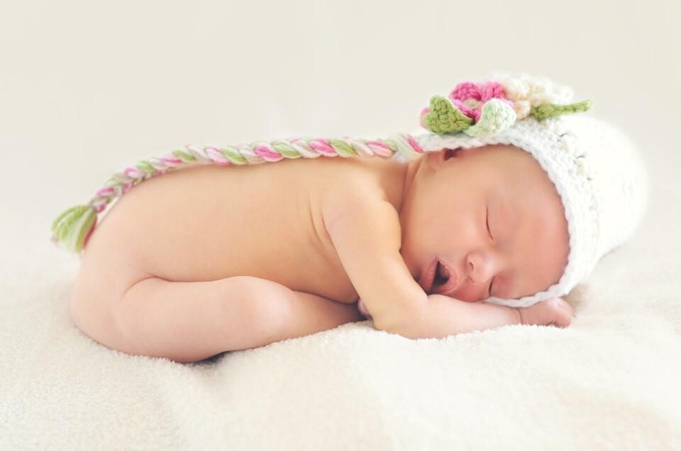 Happy sleeping baby doing yoga